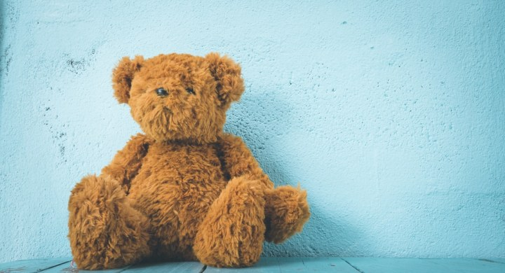 Brown teddy bear on blue background