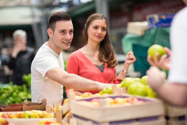 Young couple buying fruit at a market