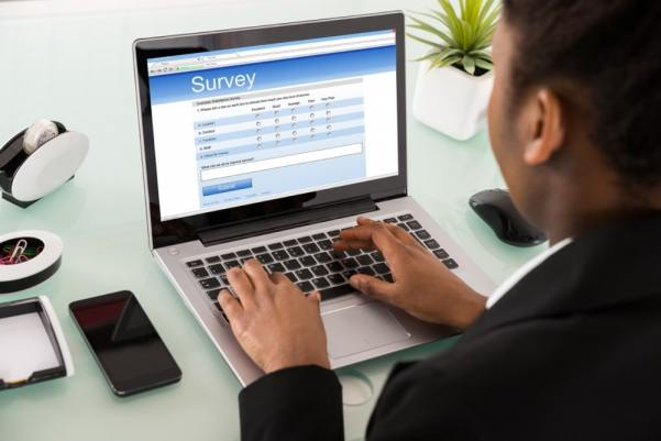 Business man completing online surveys on a laptop