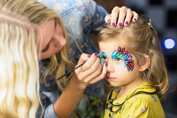 Woman painting childs face