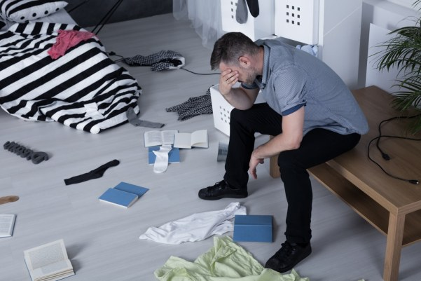 Man despairing in ransacked house