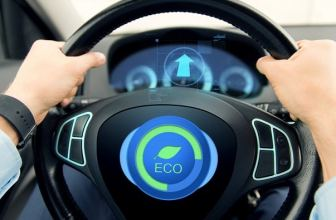 """Hands on a steering wheel with """"Eco"""" symbol in the middle"""