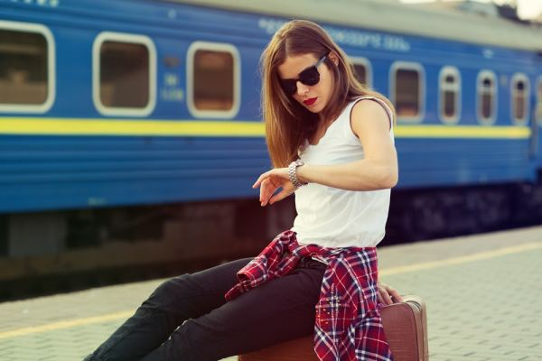 Woman looking at her watch waiting for a train