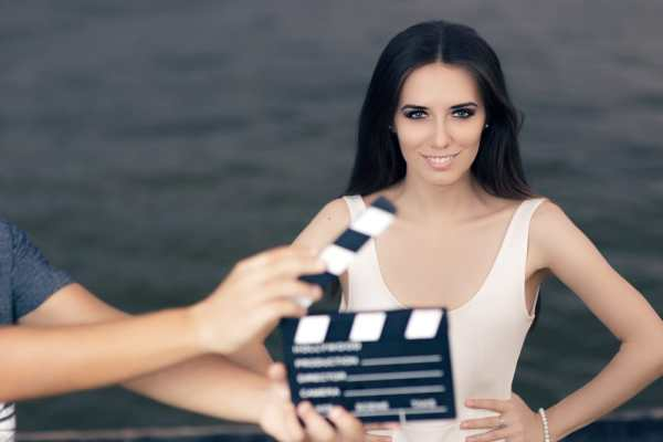 Actress standing behind clapper board