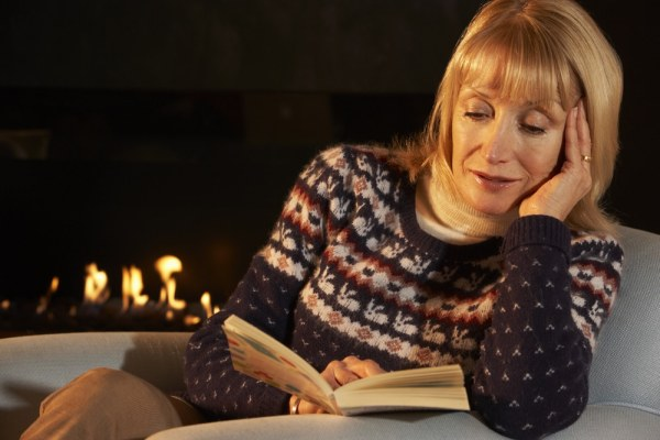 Mature woman reading in front of a fire