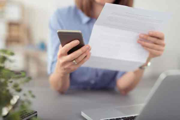 Woman looking at phone bill