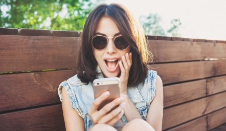Excited young woman using a mobile phone