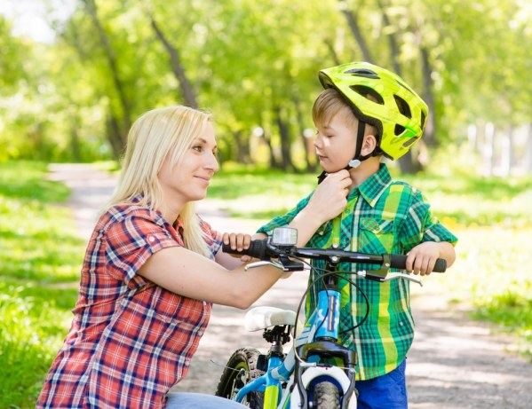 Mother putting bicycle helmet on young son