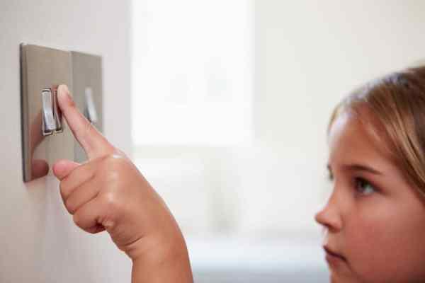 Little girl pressing light switch