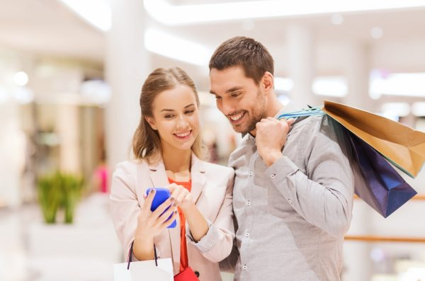 Young couple looking at a mobile while shopping