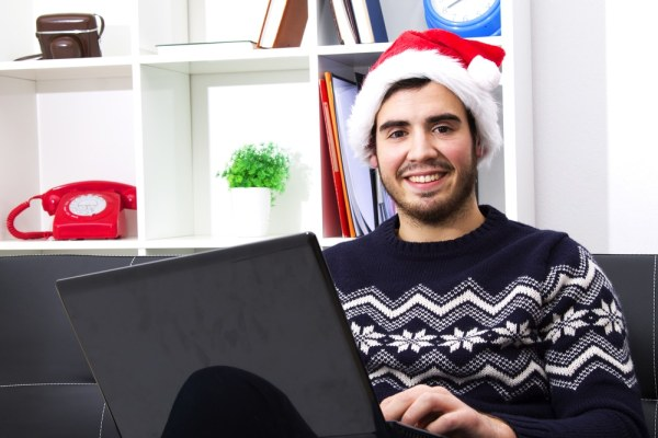 Young man in santa hat using laptop
