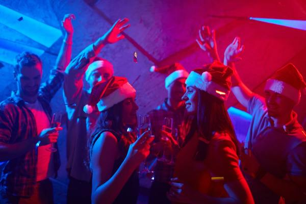 Group dancing in a club wearing santa hats