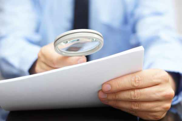 Man looking at small print on a document with a magnifying glass