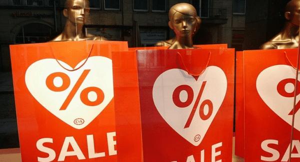 shop window mannequins holding sale signs