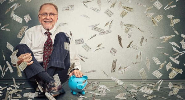 elderly business man excited surrounded by falling dollars