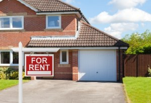 largedetached house with driveway with for rent sign in front