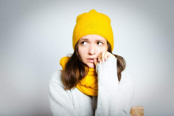 Woman in winter knits looking worried