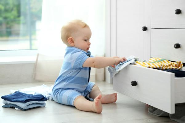 Baby putting clothes in a drawer