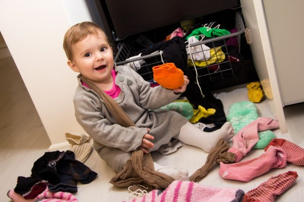 Toddler sat on floor surrounded by clutter