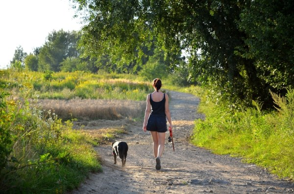 Woman walking her dog in a field