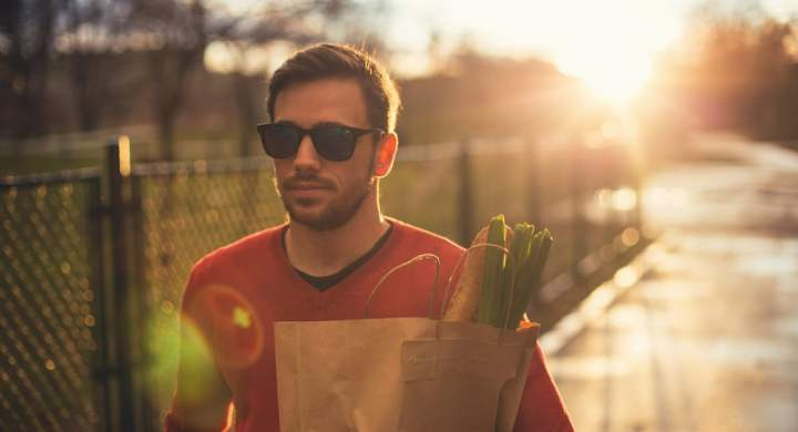 Man walking in the sunshine with groceries