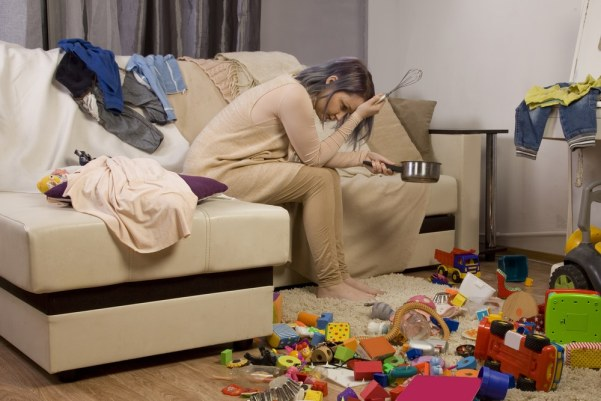 Fed up mother sat on sofa surrounded by clutter/mass