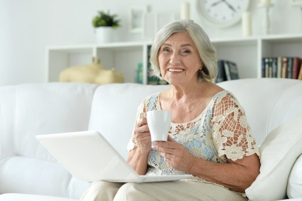 Senior woman sat in her living room with a laptop