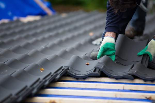 Builder laying roofing tiles