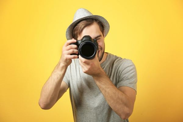 Young photographer on yellow background