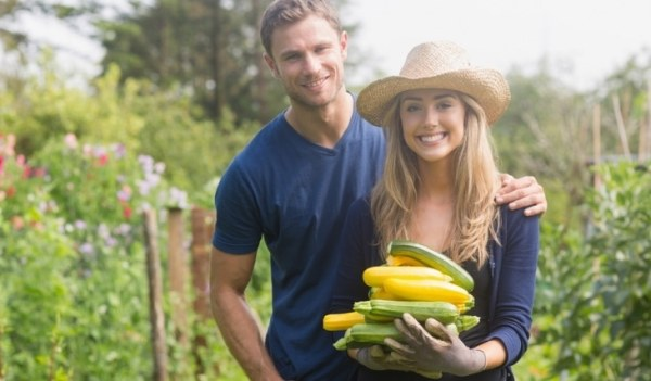 Happy couple holding home grown crops