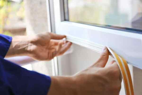 Someone applying insulation tape to windows