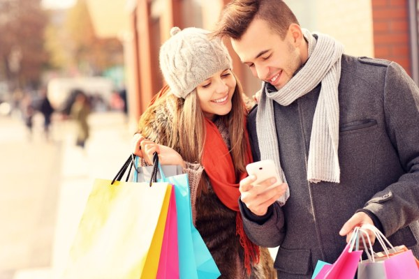 Man and woman holding shopping bags looking at phone