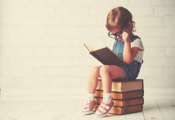 Little girl sat on stack of old books reading