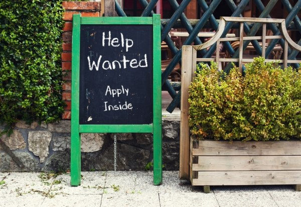 Help Wanted written on chalk sandwich board outside restaurant
