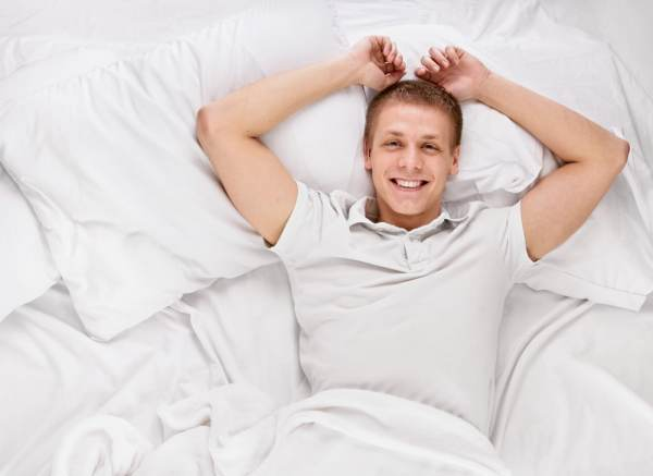 Happy man relaxing in bed