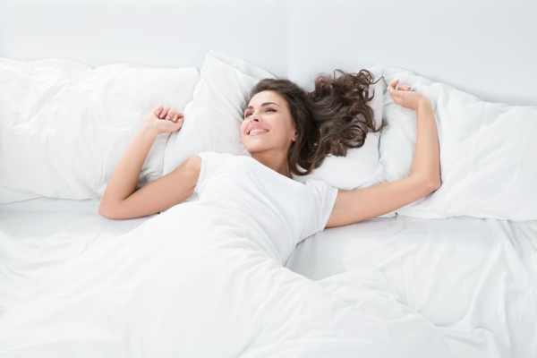 Woman relaxing happily in bed