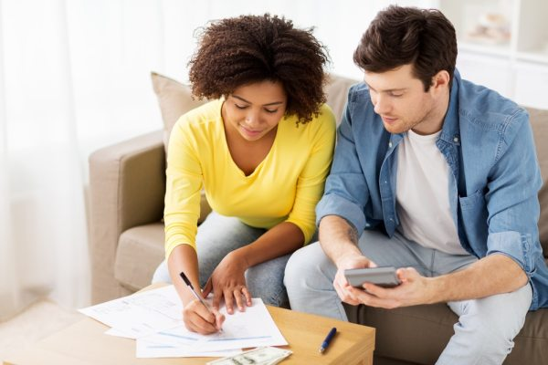 Happy mixed race couple doing finances