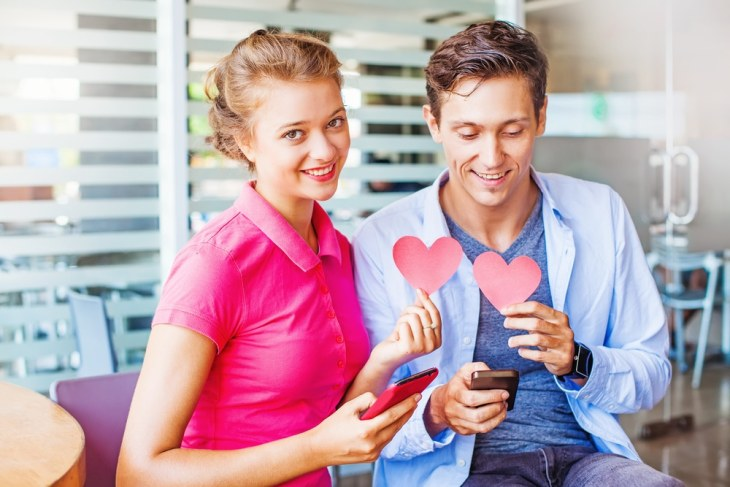Man and woman holding phones and love hearts