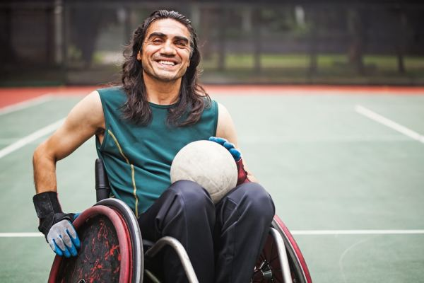 Happy wheelchair bound man playing basketball