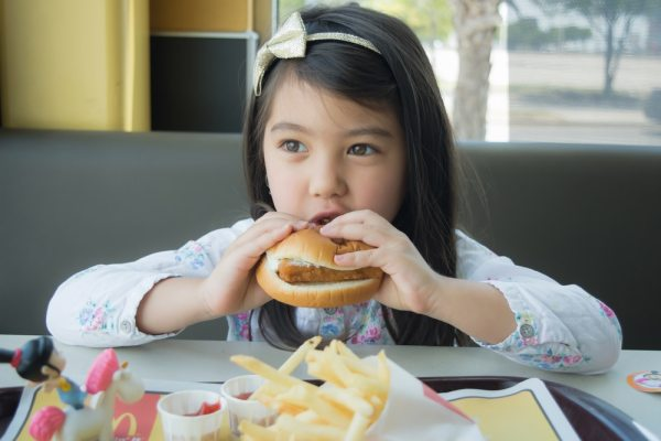 Little girl eating McDonalds burget in restaurant