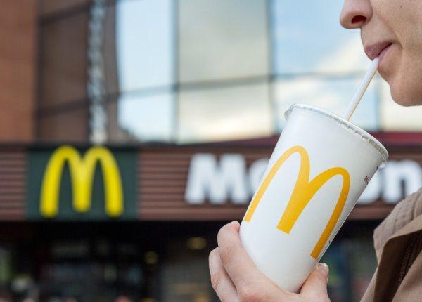Man drinking McDonalds branded drink outside restaurant