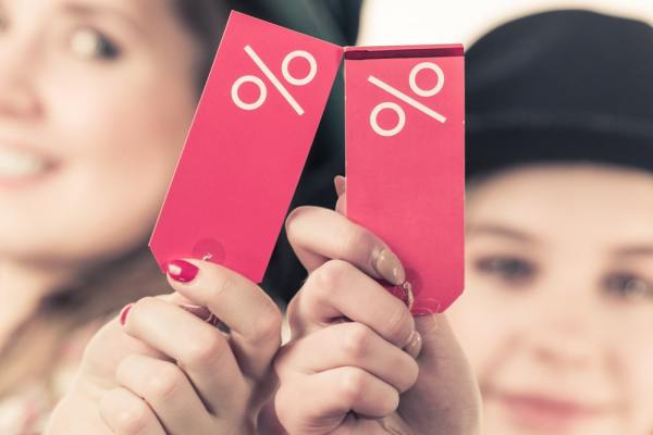 2 women holding tags with percentage symbols on