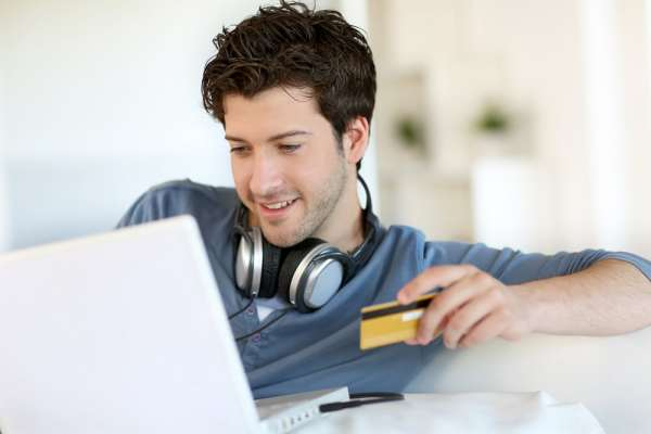 Young male student using credit card to make purchase online