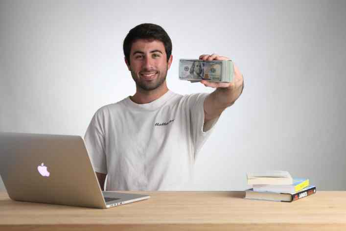 Zach is pictured holding a stack of $100 bills to invest