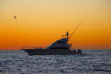 Picture of fishing yacht with an orange sunrise in the background