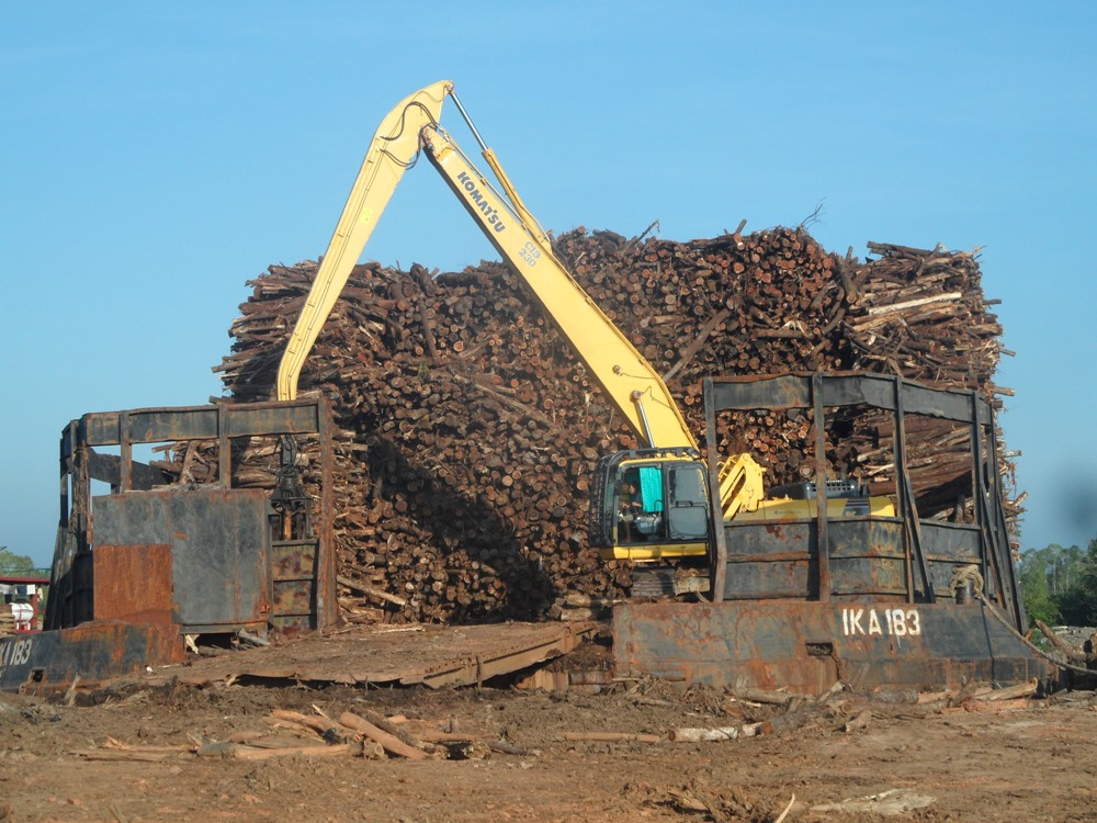 Alat berat milik satu perusahaan di Sumatera Selatan mengatur kayu hasil dari hutan alam. Foto : Wahana Bumi Hijau