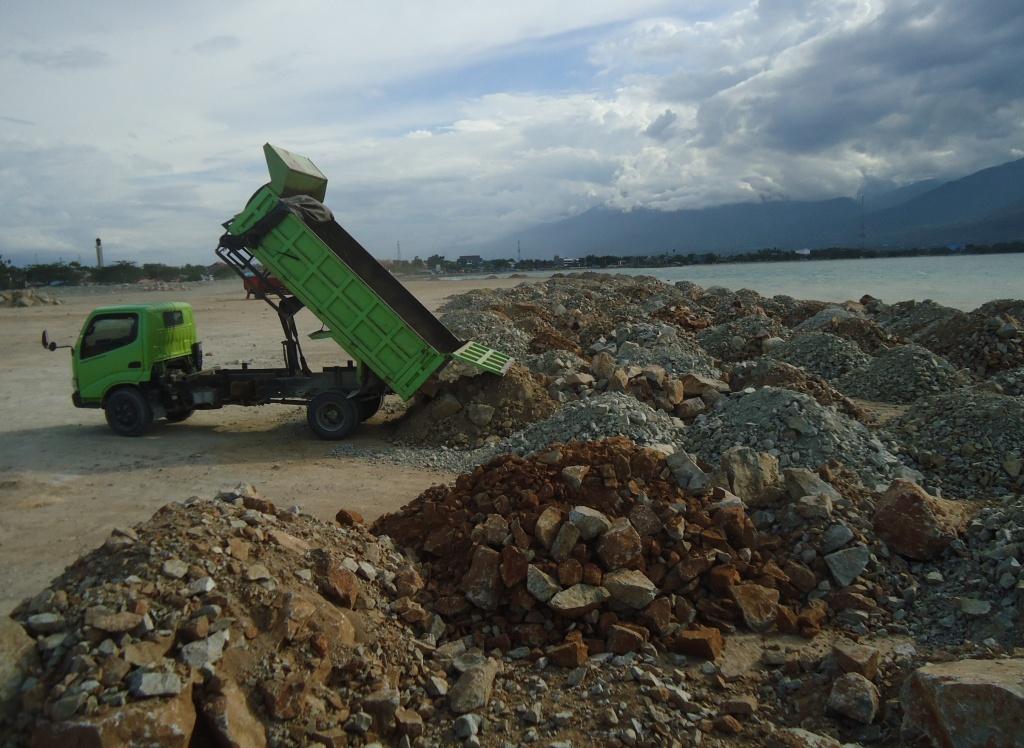Aktivitas truk menumpahkan material untuk reklamasi di Teluk Palu, Sulawesi Tengah. Berbagai pihak menentang reklamasi Teluk Palu karena merusak lingkungan. Foto : Themmy Doaly