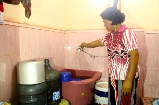 Junita, warga Gang Pelita cukup memutar keran untuk memperoleh air bersih. Foto: Tommy Apriando