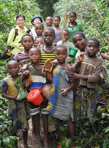 Researchers joined by local children on the way back from bonobo observations in the forest. Photo by Takeshi Furuichi