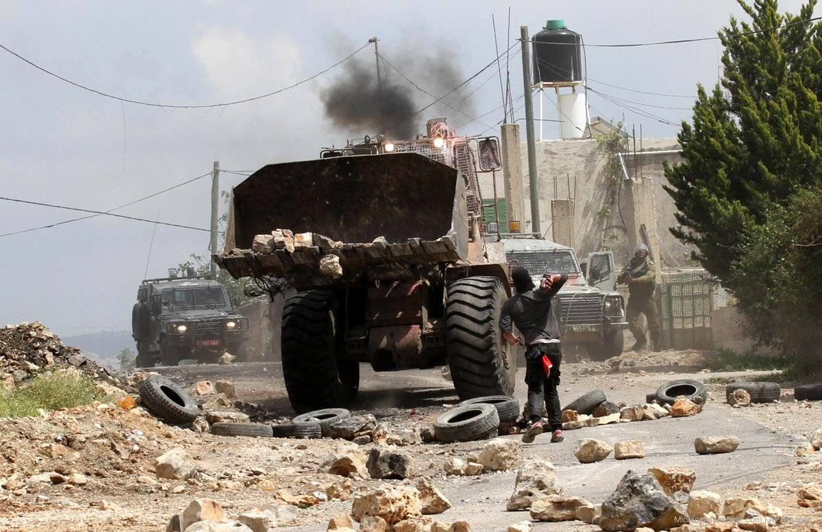 Un manifestante palestino arroja piedras contra un bulldozer israelí en Nablús, Cisjordania.